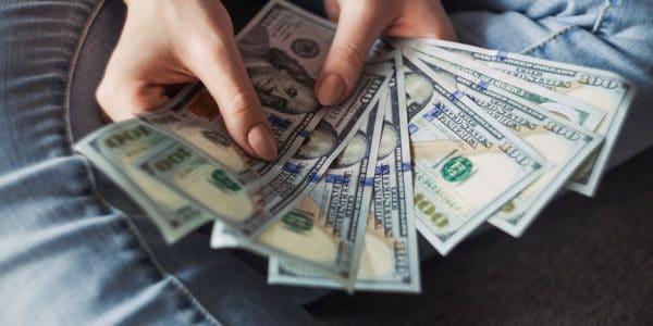 A person sitting on floor hold a fan of 100 dollar bills