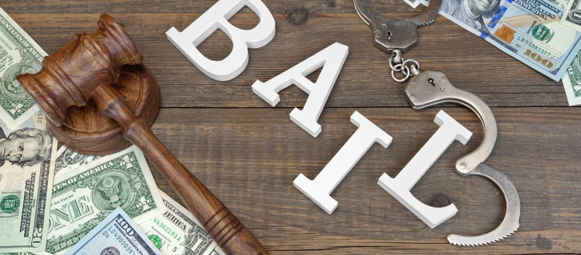 Judges Gavel, White Sign BAIL From Wooden Letters, Real Police Shabby Handcuffs And American Dollar Cash On Rough Wood Background, Top View