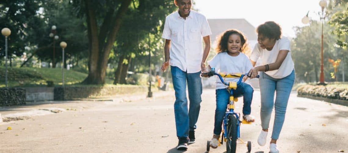 Little Girl Riding a Biycle with Training Wheels with Mom and Dad