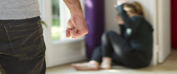 domestic violence bail bonds - man with clinched fist with a woman on floor with hands covering face jpg