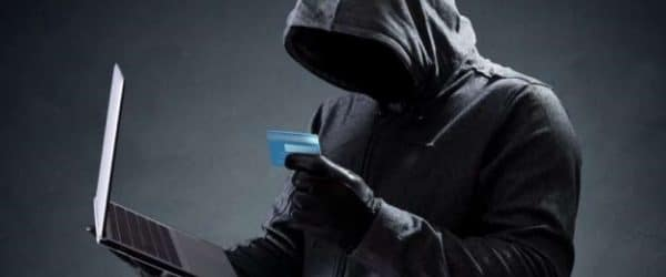 identity theft bail bonds - person with hoodie on holding a laptop and a credit card