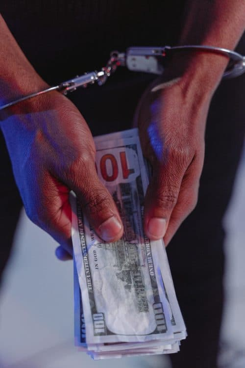 persons hands in handcuffs with 100 dollar bills